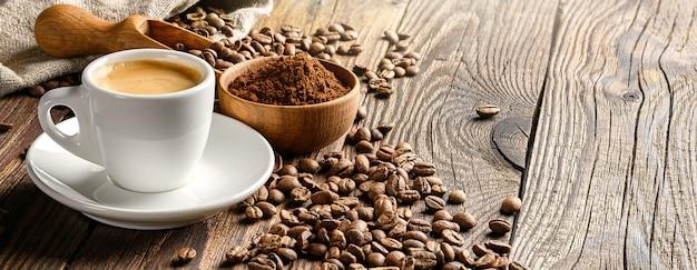 Xícara de café e feijão na velha mesa de madeira.