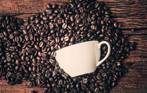 Xícara de café e feijão no fundo madeira