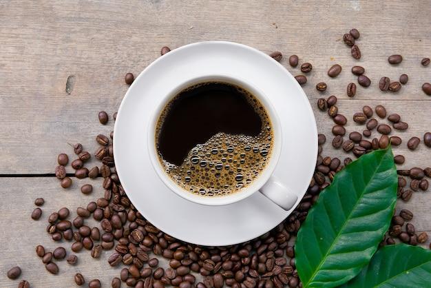 Xícara de café e feijão no fundo preto da mesa de madeira. vista do topo