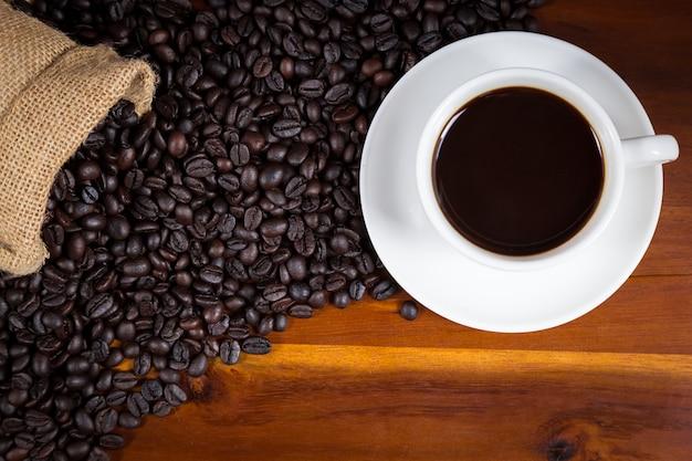 Xícara de café e feijões de café em um saco no fundo de madeira, vista superior.