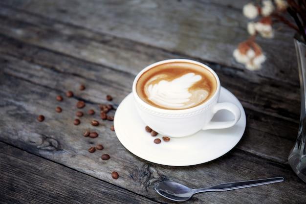 Xícara de café e flor em um vaso.