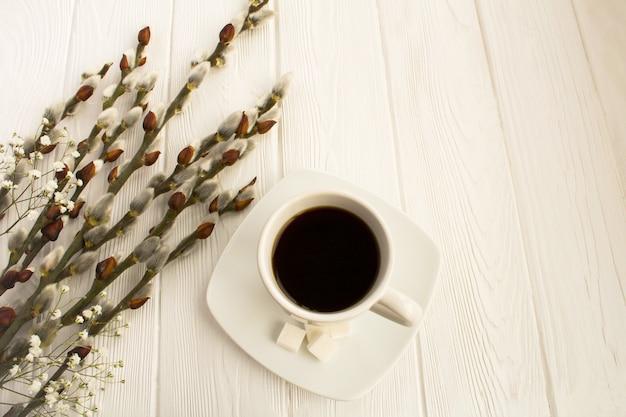 Xícara de café e flores da primavera em fundo branco de madeira. vista superior.