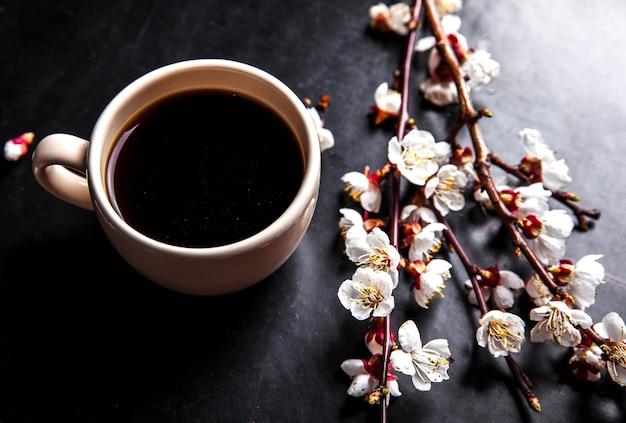 Xícara de café e flores de cerejeira rosa