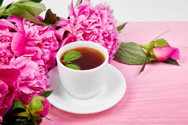 Xícara de café e flores de peônia buquê