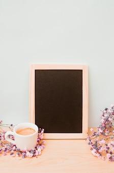 Xícara de café e flores de respiração do bebê perto da ardósia de madeira em branco contra a parede branca