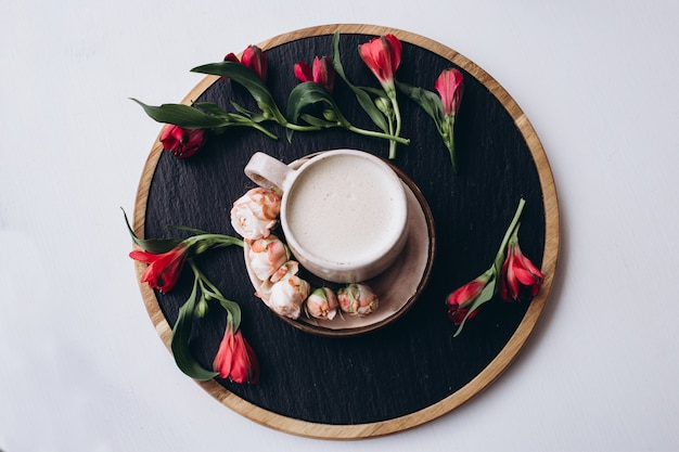 Xícara de café e flores na mesa de madeira escura no café