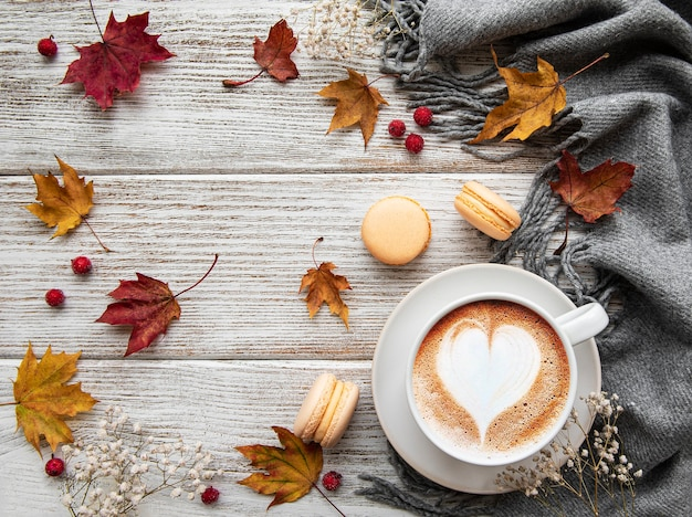 Xícara de café e folhas secas em fundo branco de madeira. camada plana, vista superior, espaço de cópia