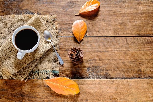 Xícara de café e folhas secas fundo