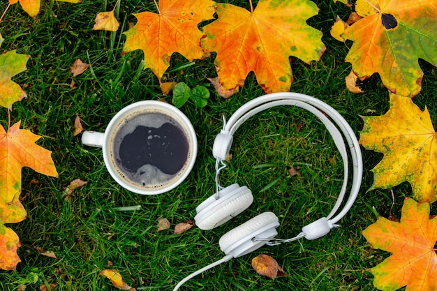 Xícara de café e fones de ouvido com folhas de plátano em uma grama verde em um jardim