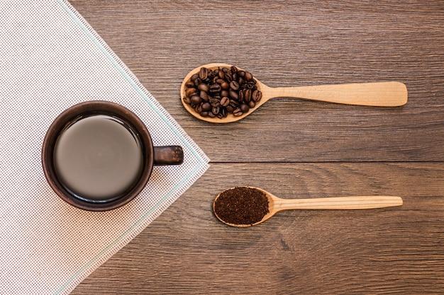 Xícara de café e grãos de café em colheres de madeira