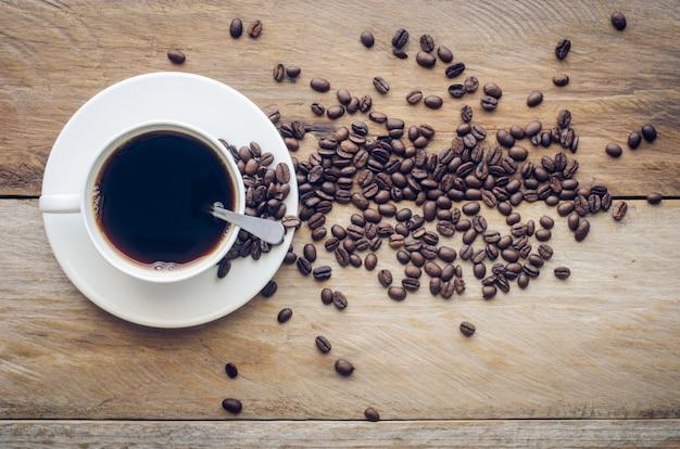 Xícara de café e grãos de café em um fundo de madeira