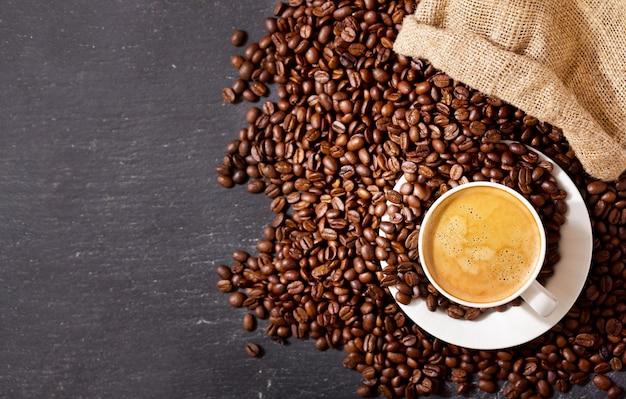 Xícara de café e grãos de café em um saco em fundo escuro, vista superior
