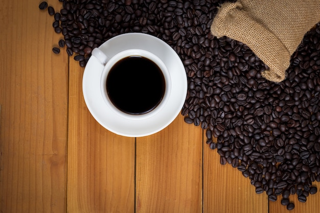 Xícara de café e grãos de café em um saco na madeira
