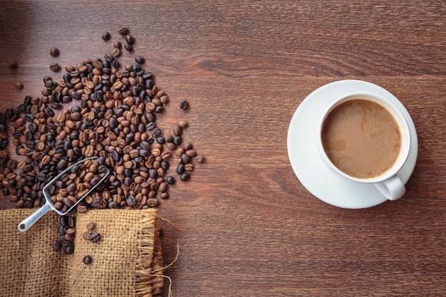 Xícara de café e grãos de café em um saco, vista de cima