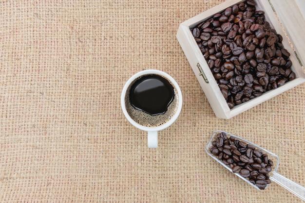 Xícara de café e grãos de café em um saque difícil