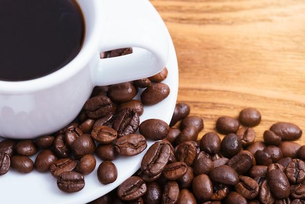 Xícara de café e grãos de café espalhados