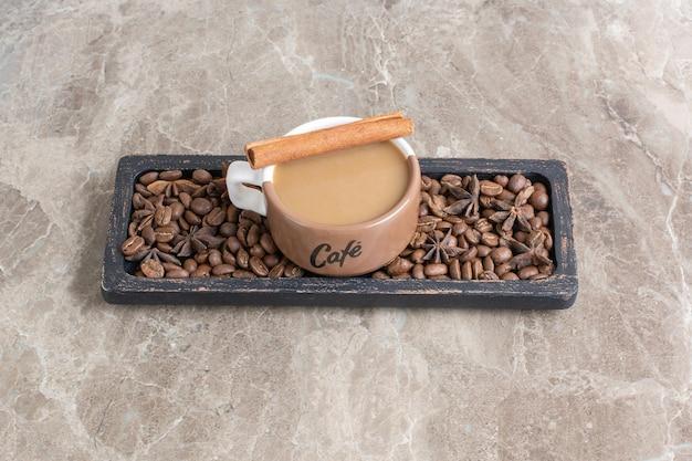 Xícara de café e grãos de café na placa escura. foto de alta qualidade