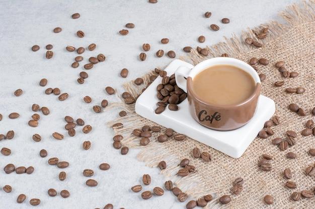 Xícara de café e grãos de café na serapilheira. foto de alta qualidade