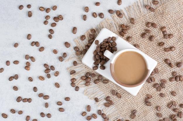 Xícara de café e grãos de café na serapilheira.