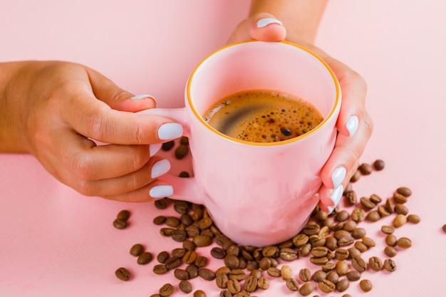 Xícara de café e grãos de café na superfície rosa