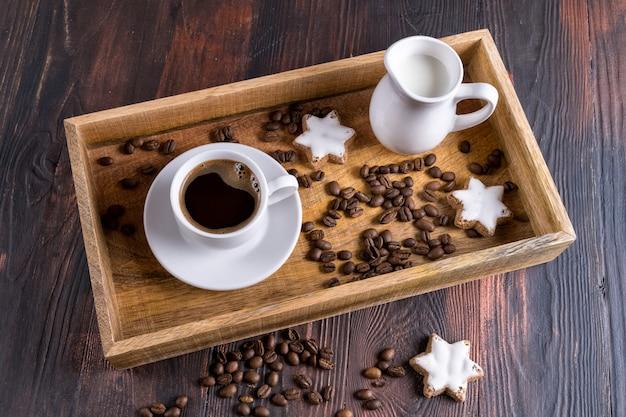 Xícara de café e grãos de café próximos em uma caixa de madeira em um fundo escuro de madeira.