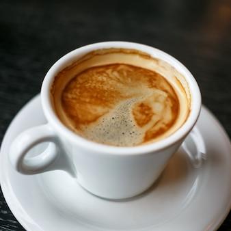 Xícara de café e grãos em uma superfície preta.
