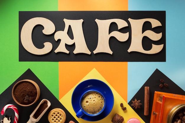 Xícara de café e ingredientes em superfície colorida