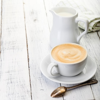 Xícara de café e jarro de leite na velha mesa de madeira pintada de branco