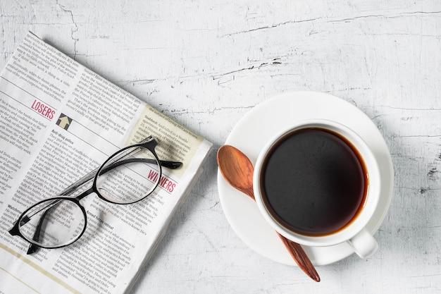 Xícara de café e jornal da manhã na mesa de madeira branca