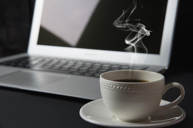 Xícara de café e laptop em cima da mesa