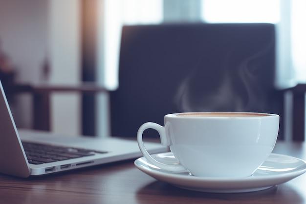 Xícara de café e laptop na mesa de madeira com assento vazio