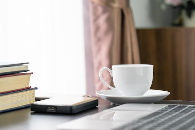 Xícara de café e laptop na mesa