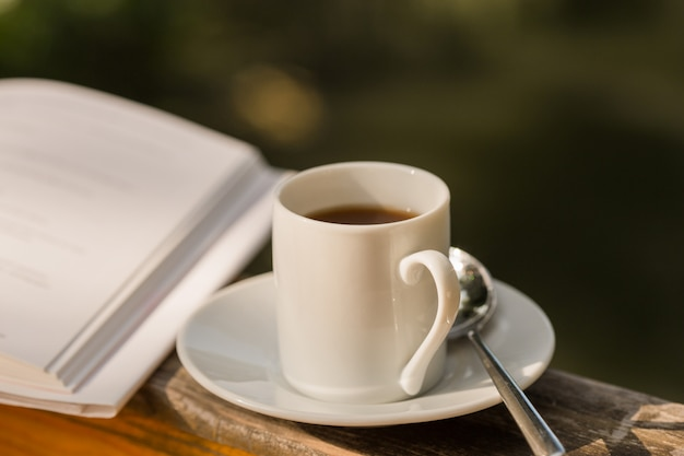 Xícara de café e livro aberto na mesa de madeira natural ao ar livre