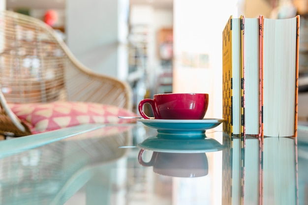 Xícara de café e livro fechado na mesa de vidro reflexivo