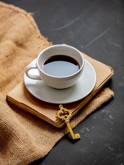 Xícara de café e livro vintage com chave em uma mesa escura