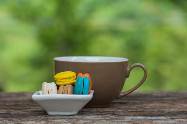 Xícara de café e macaroons coloridos no prato na mesa de madeira