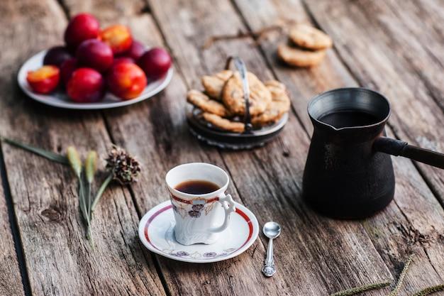 Xícara de café e maconha com diferentes petiscos saborosos na madeira.