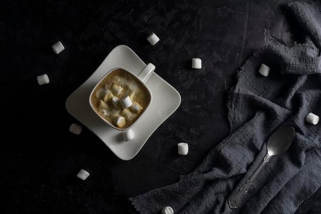 Xícara de café e marshmallows em fundo preto.