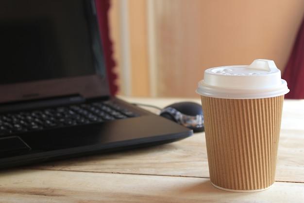Xícara de café e mesa de escritório com computador portátil