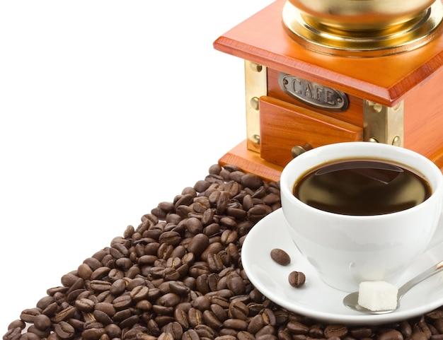 Xícara de café e moedor de feijão isolado no fundo branco
