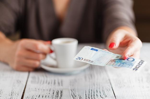 Xícara de café e nota de 20 euros