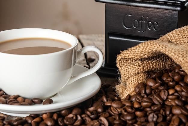 Xícara de café e pilha de feijão em uma mesa de madeira