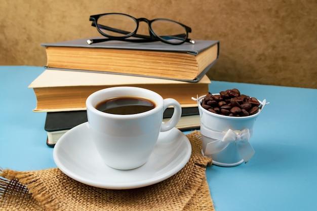 Xícara de café e pilha de livros em azul