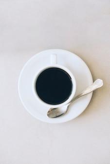 Xícara de café e pires com colher em pano de fundo branco