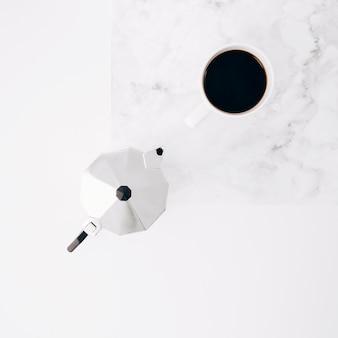 Xícara de café e pote no plano de fundo texturizado branco