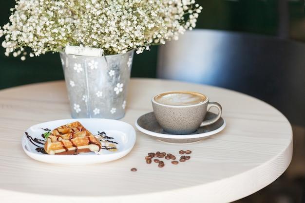 Xícara de café e prato de waffles belgas em uma mesa de madeira leve em um café
