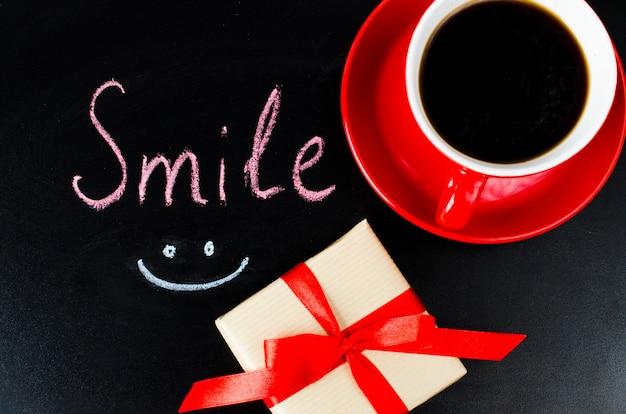 Xícara de café e presente. inscrição sorriso.