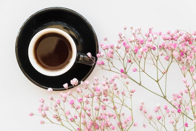 Xícara de café e ramos rosa