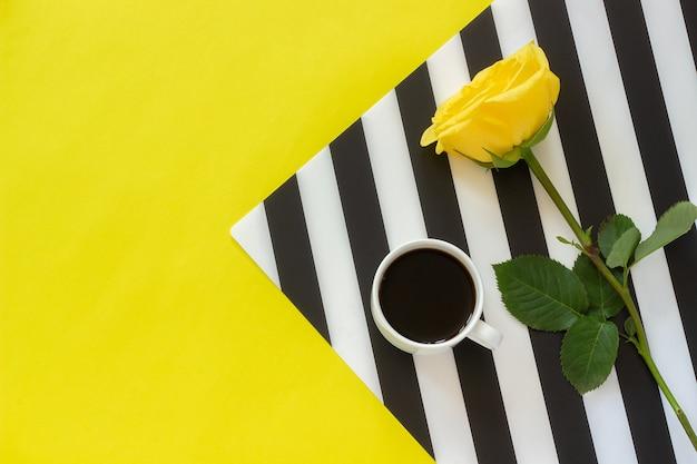 Xícara de café e rosa do amarelo no guardanapo preto e branco à moda no fundo amarelo.