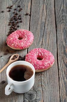 Xícara de café e rosquinhas rosa com granulado na velha mesa de madeira